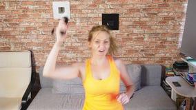 Tir moyen d'une femme dansant au jeu vidéo dans un arrangement à la maison 4k, mouvement lent banque de vidéos