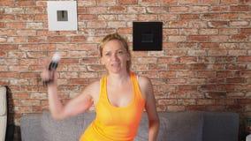 Tir moyen d'une femme dansant au jeu vidéo dans un arrangement à la maison 4k, mouvement lent clips vidéos