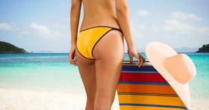 Tir moyen d'une jeune fille blanche se tenant à côté de sa chaise longue dans son bikini jaune images libres de droits