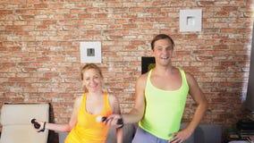 Tir moyen des couples, d'un homme et d'une femme dansant au jeu vidéo dans un arrangement à la maison 4k, mouvement lent clips vidéos
