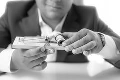 Tir noir et blanc d'homme d'affaires tenant la souricière à clapet avec l'argent Images stock