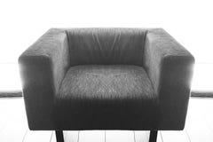 Tir noir et blanc d'un fauteuil de vintage sur le plancher contre la grande fenêtre Photo stock