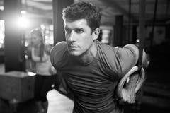 Tir noir et blanc de l'homme s'exerçant avec les anneaux gymnastiques images stock
