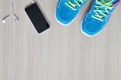 tir plat de configuration des écouteurs et du téléphone d'espadrilles de sport Images stock
