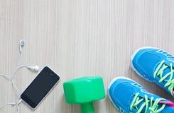 Tir plat de configuration des écouteurs et du téléphone d'espadrilles de sport sur le Ba en bois Photos stock