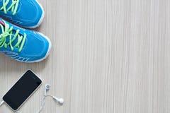 Tir plat de configuration des écouteurs et du téléphone d'espadrilles de sport sur le Ba en bois Images stock