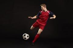 Tir professionnel de footballeur au but dans le studio photographie stock libre de droits