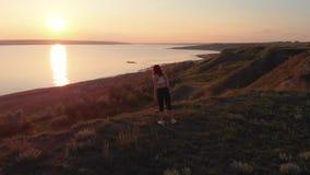 Tir a?rien de la jeune femme sportive faisant des exercices sur l'egde de la pente pr?s du lac ou du liman pendant le beau lever  clips vidéos