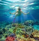 Tir sous-marin d'une femme naviguant au schnorchel au soleil Photographie stock