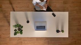 Tir supérieur, vie de bureau de laps de temps, homme focalisé travaillant à l'aide de l'ordinateur portable, café potable et traî banque de vidéos