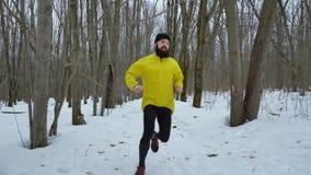 Tir tenu dans la main d'homme barbu de sports dans le manteau jaune fonctionnant dans la forêt d'hiver clips vidéos