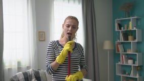 Tir tenu dans la main de jeune femme chantant une chanson utilisant un balai comme microphone banque de vidéos