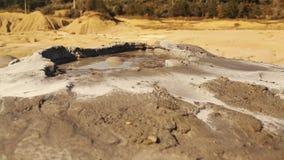Tir ultra en gros plan d'un volcan de boue dans un village à distance