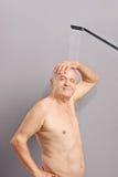 Tir vertical d'un aîné gai prenant une douche Image stock