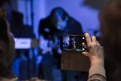 Tir visuel avec votre smartphone Pelliculage du concert Musiciens jouant la double basse et la guitare électrique images stock