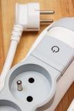 Tira da corrente elétrica com interruptor -fora no assoalho de madeira Imagem de Stock