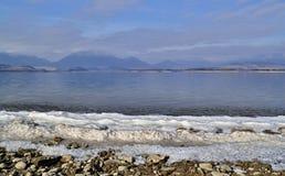Tira da neve na costa do lago com as montanhas no fundo Fotografia de Stock Royalty Free