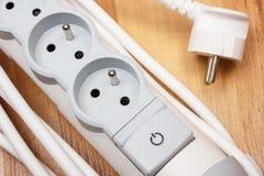 Tira de la corriente eléctrica con el interruptor encendido-apagado en piso de madera Foto de archivo libre de regalías