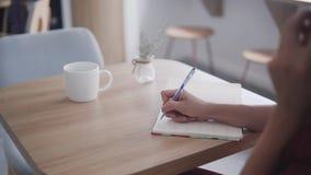 Tirado arriba de las manos de la mujer de negocios acertada hermosa y joven con la libreta en un café, trabajando como freelancer almacen de metraje de vídeo
