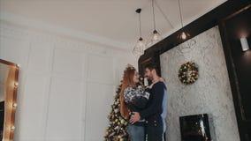 Tirado de debajo de un par encantador del yound en el amor huging en el fondo del árbol de navidad almacen de metraje de vídeo
