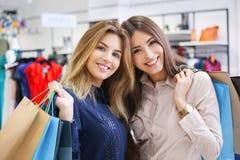 Tirado de hacer compras que va hermoso de las mujeres jovenes Imagen de archivo libre de regalías