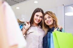 Tirado de hacer compras que va hermoso de las mujeres jovenes Foto de archivo libre de regalías
