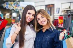Tirado de hacer compras que va hermoso de las mujeres jovenes Imagenes de archivo