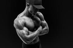 Tirado de hombre joven muscular sano con el casquillo negro del beseball Fotos de archivo libres de regalías