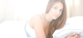 Tirado de la mujer joven hermosa que lee un mensaje de texto mientras que miente en su cama Fotos de archivo