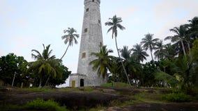 Tirado de la tierra del faro hermoso que se coloca en una colina en una isla tropical almacen de metraje de vídeo