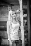 Tirado de muchacha hermosa cerca de una cerca de madera vieja Desgaste elegante de la mirada: top básico blanco, vaqueros del dri Fotos de archivo libres de regalías