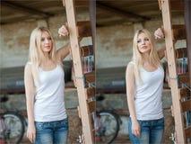 Tirado de muchacha hermosa cerca de una cerca de madera vieja Desgaste elegante de la mirada: top básico blanco, vaqueros del dri Foto de archivo
