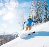 Tirado de un esquí parasitario masculino en las montañas en nieve fresca del polvo en día de invierno soleado fotos de archivo