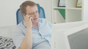 Tirado de un hombre de negocios usando un PC de sobremesa mientras que habla en el teléfono móvil almacen de video