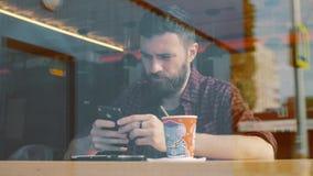Tirado de un hombre que se sienta en café con un smartphone Tirado a través de ventana de demostración del café almacen de metraje de vídeo