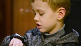 Tirado de un niño que hace la preparación y que habla con la mamá en Smartwatch metrajes