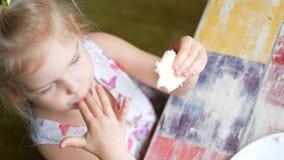 Tirado de un niño que lame la comida apagado de su finger Ella después da vuelta y sonríe almacen de video