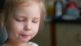 Tirado de un niño que lame la comida apagado de su finger Ella después da vuelta y sonríe almacen de metraje de vídeo