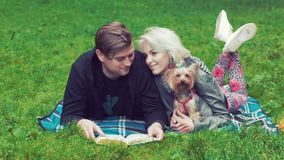 Tirado de un par joven con un perro Mienten en la hierba y discuten lo que leen adentro el libro almacen de video