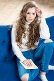 Tirado de una mujer hermosa en un suéter y de vaqueros en el sofá Imagen de archivo libre de regalías