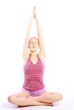Tirado de una mujer joven deportiva que hace ejercicio de la yoga. Imágenes de archivo libres de regalías