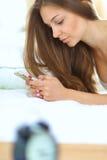 Tirado de una mujer joven hermosa que lee un mensaje de texto mientras que miente en su cama Imágenes de archivo libres de regalías