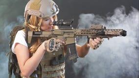 Tirador de la muchacha en rifle de francotirador de la tenencia del engranaje del francotirador a disposición en el fondo ahumado metrajes