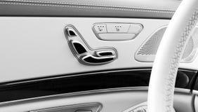 Tirador de puerta con los botones del contol del asiento del poder de un vehículo de pasajeros de lujo Interior del cuero blanco  Foto de archivo