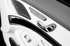 Tirador de puerta con los botones del contol del asiento del poder de un vehículo de pasajeros de lujo Interior del cuero blanco  Imagenes de archivo