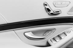 Tirador de puerta con los botones del control del asiento del poder de un vehículo de pasajeros de lujo Interior del cuero blanco Foto de archivo libre de regalías