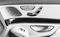 Tirador de puerta con los botones del control del asiento del poder de un vehículo de pasajeros de lujo Interior del cuero blanco Fotografía de archivo libre de regalías