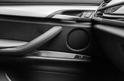 Tirador de puerta con los botones del control del elevalunas eléctrico de un vehículo de pasajeros de lujo Interior de cuero negr Foto de archivo