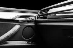 Tirador de puerta con los botones del control del elevalunas eléctrico de un vehículo de pasajeros de lujo Interior de cuero negr Imagenes de archivo