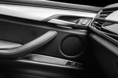 Tirador de puerta con los botones del control del elevalunas eléctrico de un vehículo de pasajeros de lujo Interior de cuero negr Foto de archivo libre de regalías